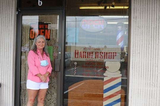 Sharon in front of her business, Sharon's Barbershop